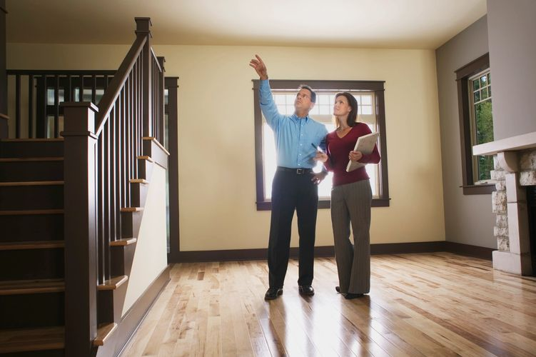 home inspector pointing something out to woman