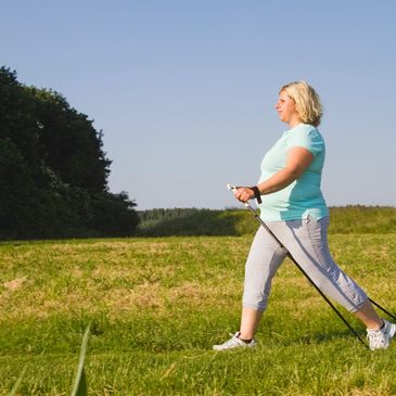 woman overweight walking doing exercises with sticks in field healthy