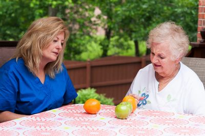 Speech language pathologist is working with an elderly patient at a table with fruit on it