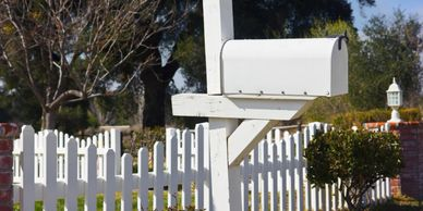 White mailbox in front of a white picket fence