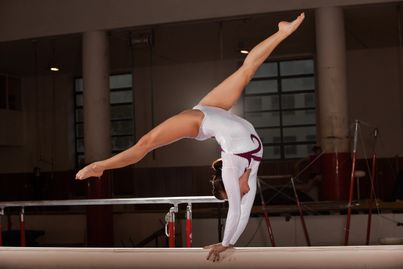 Gymnast back walkover on the beam