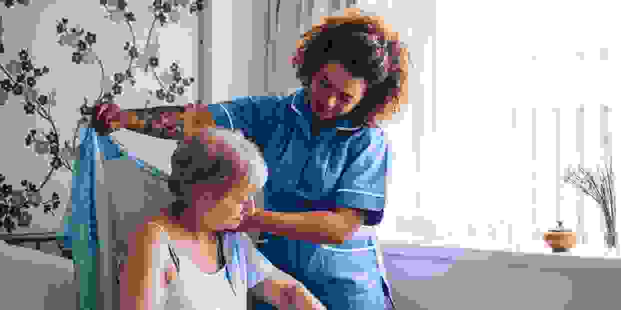 2 females pictured. Caregiver is assisting the client with putting on her blouse over her tank top.