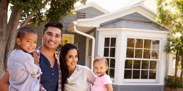 A happy family poses in front of a recently sold San Diego Home financed by the Drysdale Team.
