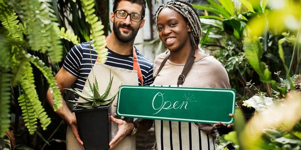 Man and woman in greenhouse holding surrounded by tropical plants holding an aloe and an open sign.