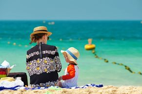 Lady and baby sitting on a beach wearing hats and looking at each other with water behind them
