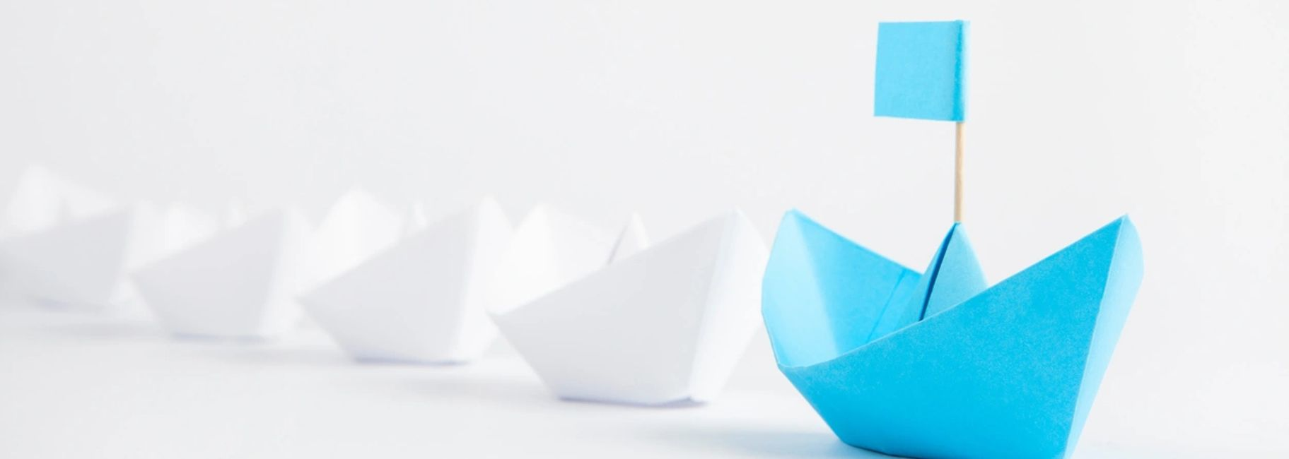 four white and one blue boat made out of paper.