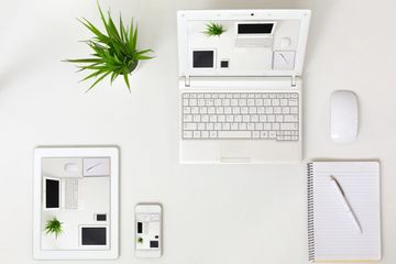 White flatlay with a laptop, tablet, phone, mouse, notebook and pen. A pot plant on the table.