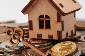 small Wooden house and key sitting on coins. Click here for specific account info