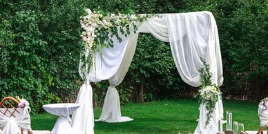 Outdoor trellis with sheer and floral arrangement