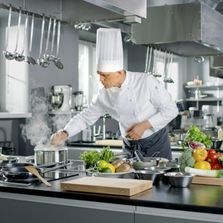 A man in a chef hat and white coat is preparing food in a restaurant kitchen.
