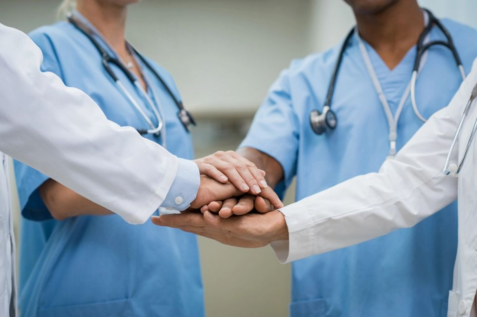 nurses and doctors putting hands together as a team