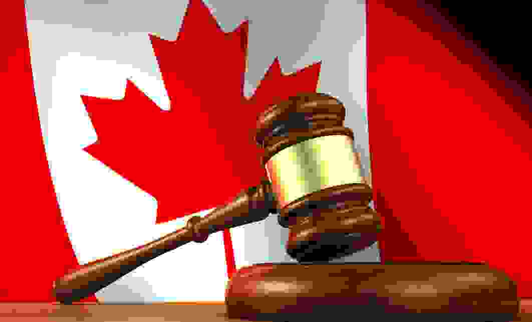 The Canadian flag with a judge's gavel in the foreground.