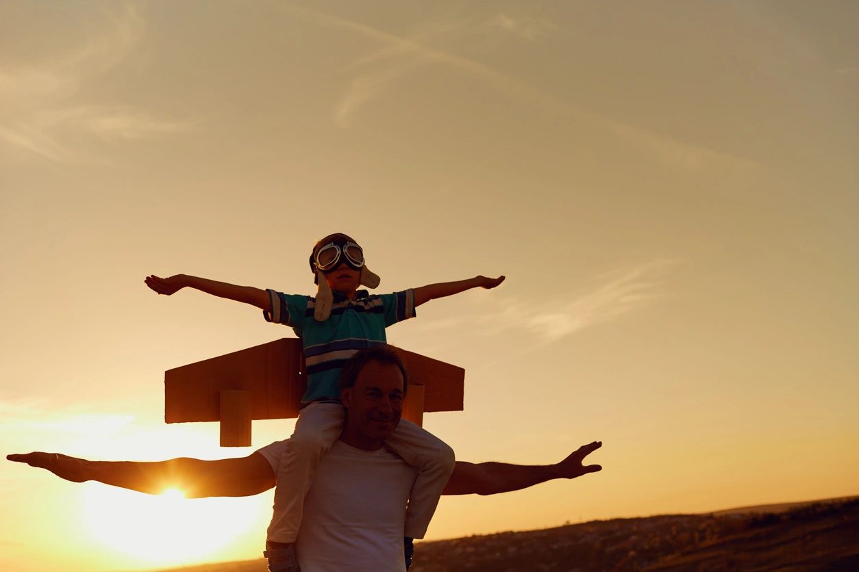 Father with son riding on his shoulders, both with arms outstretched, in blazing sun, low in the sky