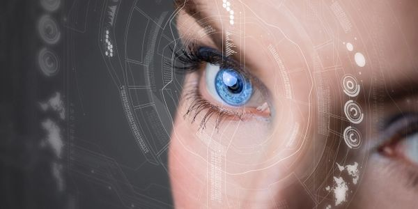 Woman's eye with white overlay of data widgets. Suggestive of new technology and analytics.