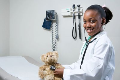 A young girl, dressed up as a doctor, uses a stethoscope on a teddy bear while smiling.
