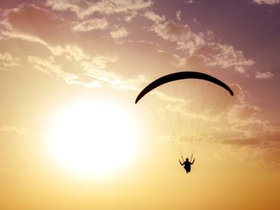 For screen readers: an image of an individual in an open parachute floating down at sunset
