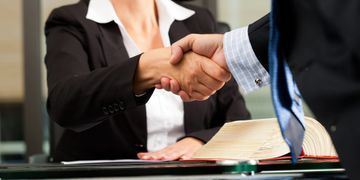 Man and woman shaking hands over documents