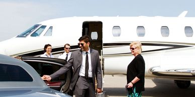 Executive getting out of a limousine ready to board his private jet