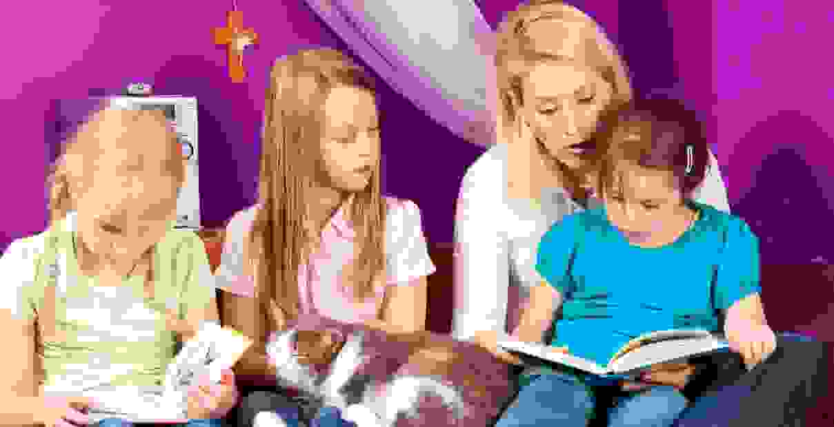 A mother is reading a book with her daughter sitting on her lap while the other 2 children watch.