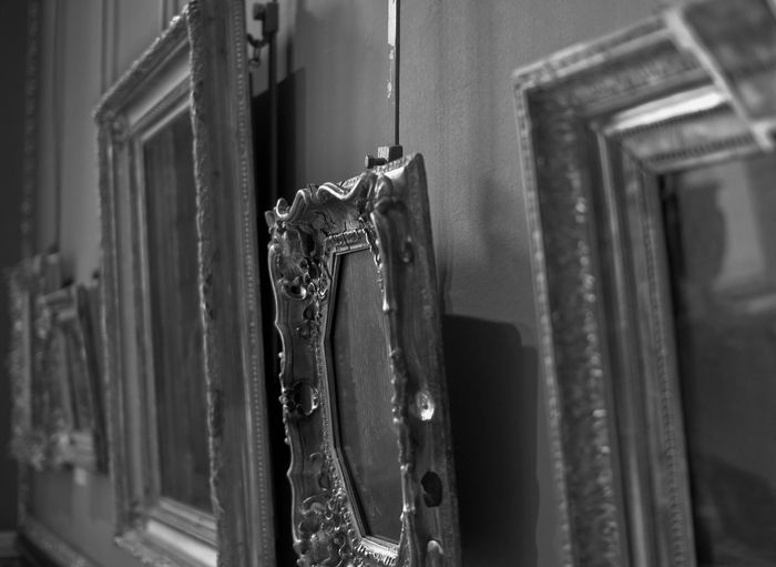 Black and white side view image of three picture frames hanging on a wall.
