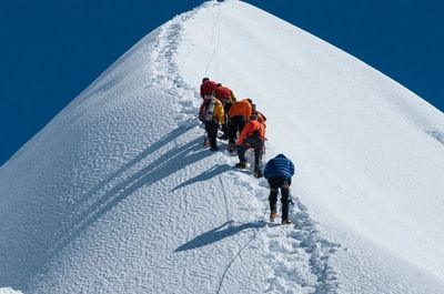 For screen readers: an image of a group of individuals hiking towards the top of a snowy hill