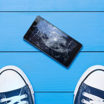 Shattered iPhone Screen on the floor in front of someone shoes.