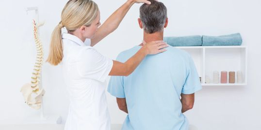 Chiropractor applying chiropractic services to an adult man