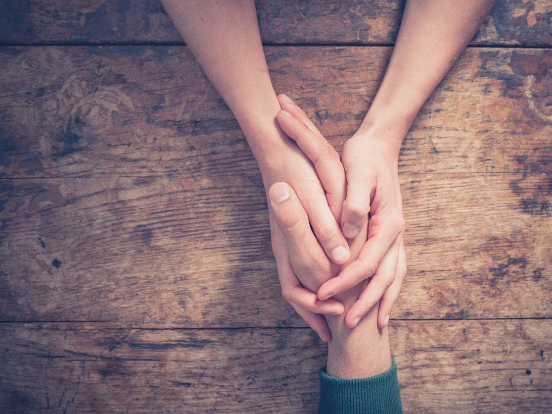 Hands holding a hand. To show we are here for you.