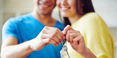 A young couple holding keys to their first home