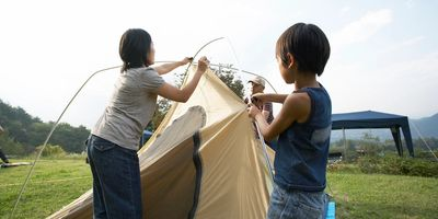 Child helps mother and family setting up a tent whilst camping in a field. They are assembling the tent poles