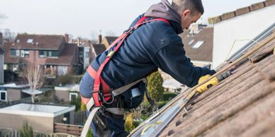 Engineer working on a roof installing solar panels wearing a safety harness