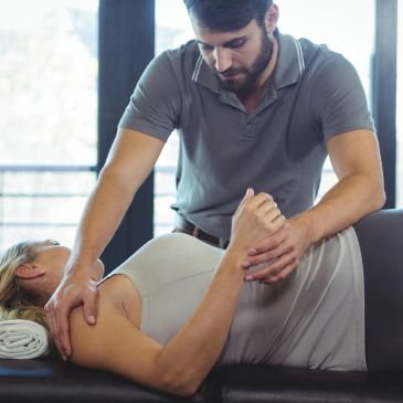 Personal trainer working with a client on her body to make sure that she is not in pain and has proper shoulder movement.