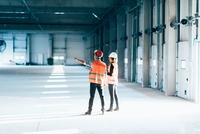 A man and a woman wearing PPE in a Warehouse discussing their doors options