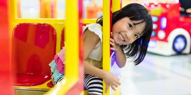 Asian girl smiling at the camera while sitting in a large toy car