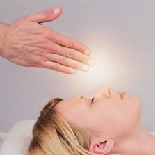 Reiki - Women with eyes closed laying down.  Hands shown over womens forhead with glowing light