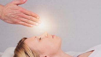 Woman laying on her back with hands clasped over her forehead with a glow of light at the tips of the fingers of the clasped hands.