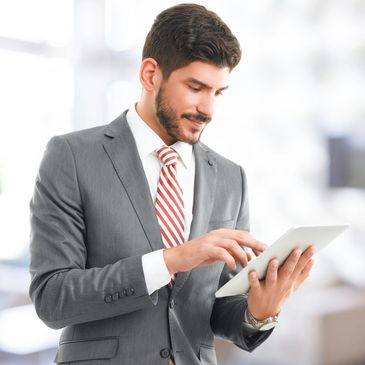 A man in a suit viewing a tablet.