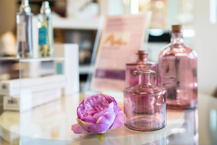 Pink perfume bottles, on perfume shop counter top.