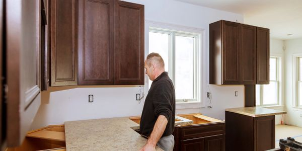 Picture of a worker installing new granite countertops.