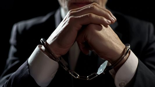 A person sitting with his hands clasped together in front of him with handcuffs on.