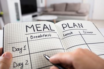 A meal planner book open with a pen.