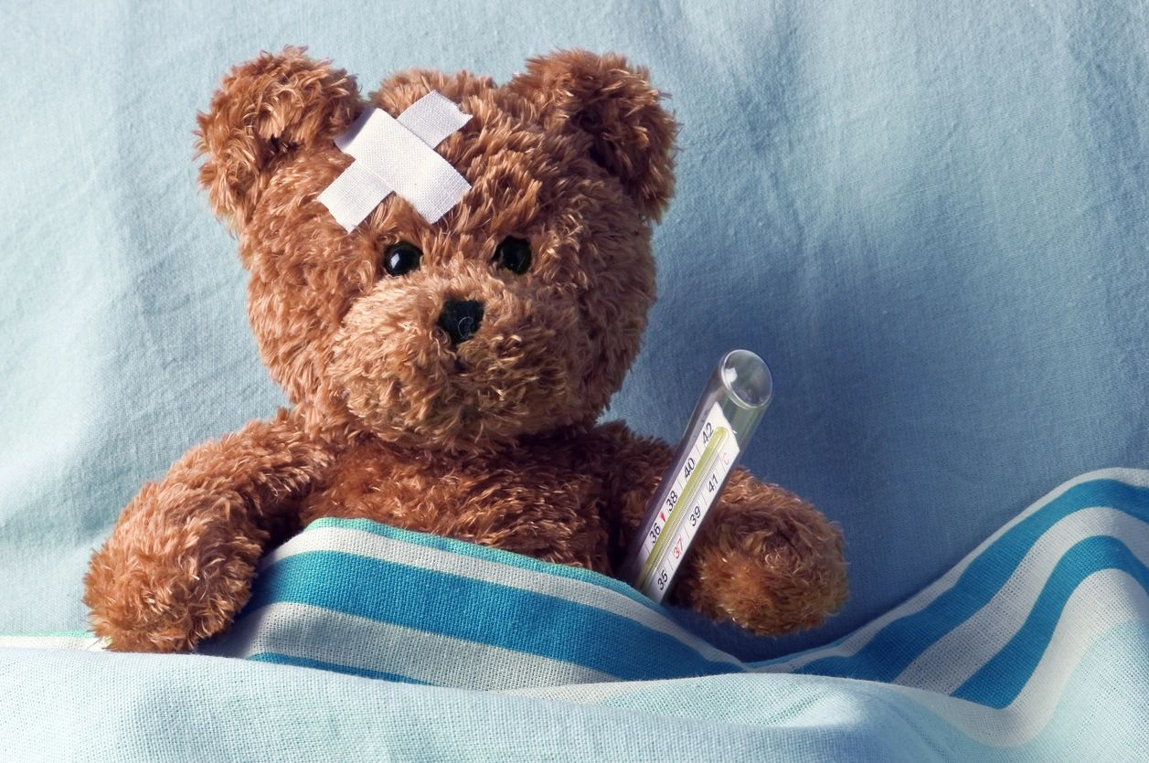 Sick teddy bear with thermometer and bandage