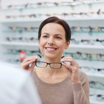 Woman putting on a pair of glasses and smiling