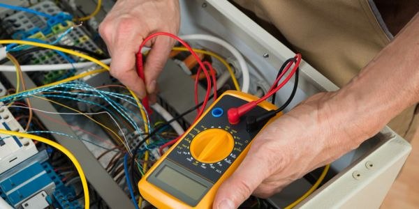 Testing electrical circuits with a multimeter by an electrician near me.