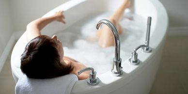 A photo of a lady in an oval bathtub with her left arm resting on the side and her right knee sticking out of the bubbles with the left foot resting on the end of the tub.  her head is resting on a folded towel.