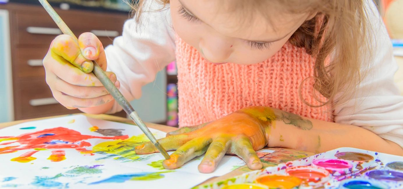 A child exploring color through paint