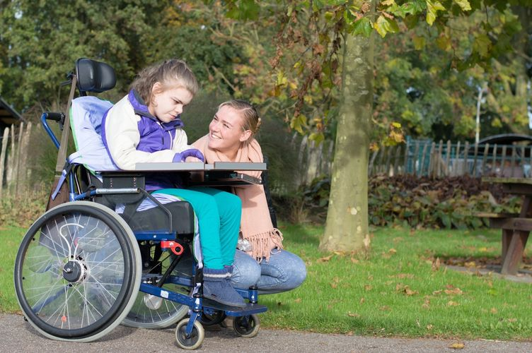 Blonde girl smiling at a girl in a wheelchair