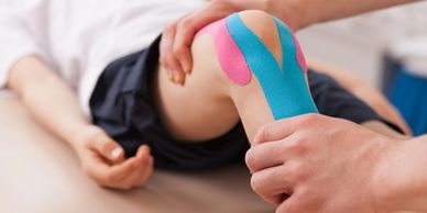 taping strapping on knee by physiotherapist