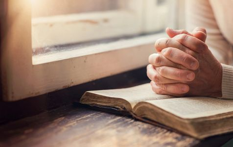 Image of praying hands an a bible.