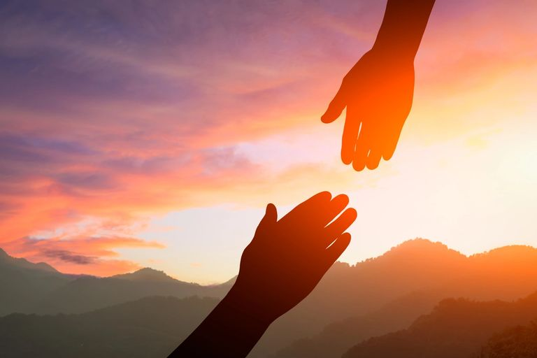Two hands reaching towards each other in a show of support.